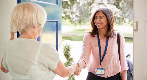 An older female shaking hands with a female doctor in her home